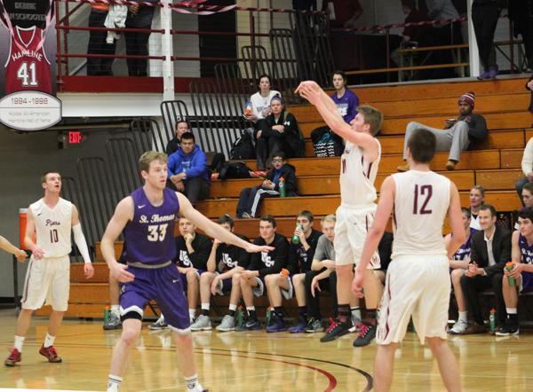 Sophomore guard Connor Knutson (12) and junior guard Zach Smith (10) look on as junior guard Bret Lukes (11) takes a shot in last seasons's 65-82 home defeat to St. Thomas.