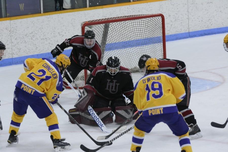 Sophomore goalie John Sellie-Hanson defends the net for the Pipers with the Pointers threatening in the defensive zone.