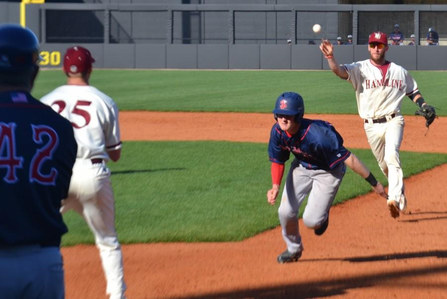 Senior shortstop Chris Zeller throws to first base to first-year pitcher Zach Smith in attempt to catch the runner in the rundown.