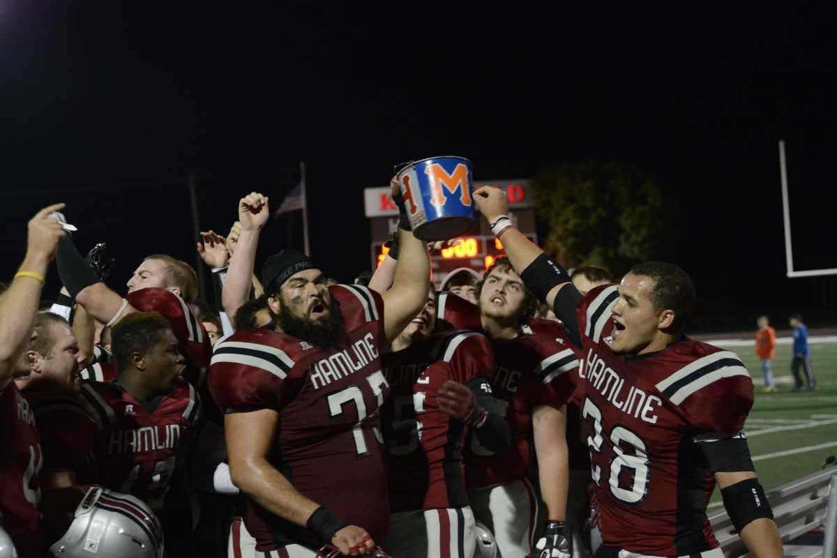 Piper football players celebrate after they win the battle for the Paint Bucket in the 2014 season. The Pipers won the bucket back after a multi-year hiatus. The Paint Bucket will stay with Hamline for another after the team beat the Scots, 27-10 on Sep. 12.