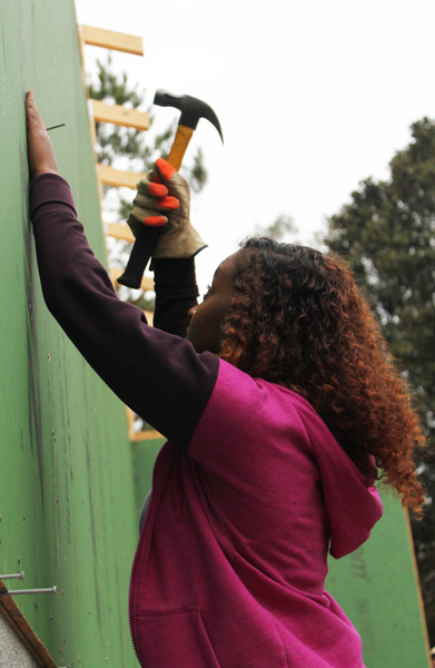 Sumaya Aden (first-year) hammering nails into the siding of the Habitat for Humanity house in Wilmington, North Carolina.