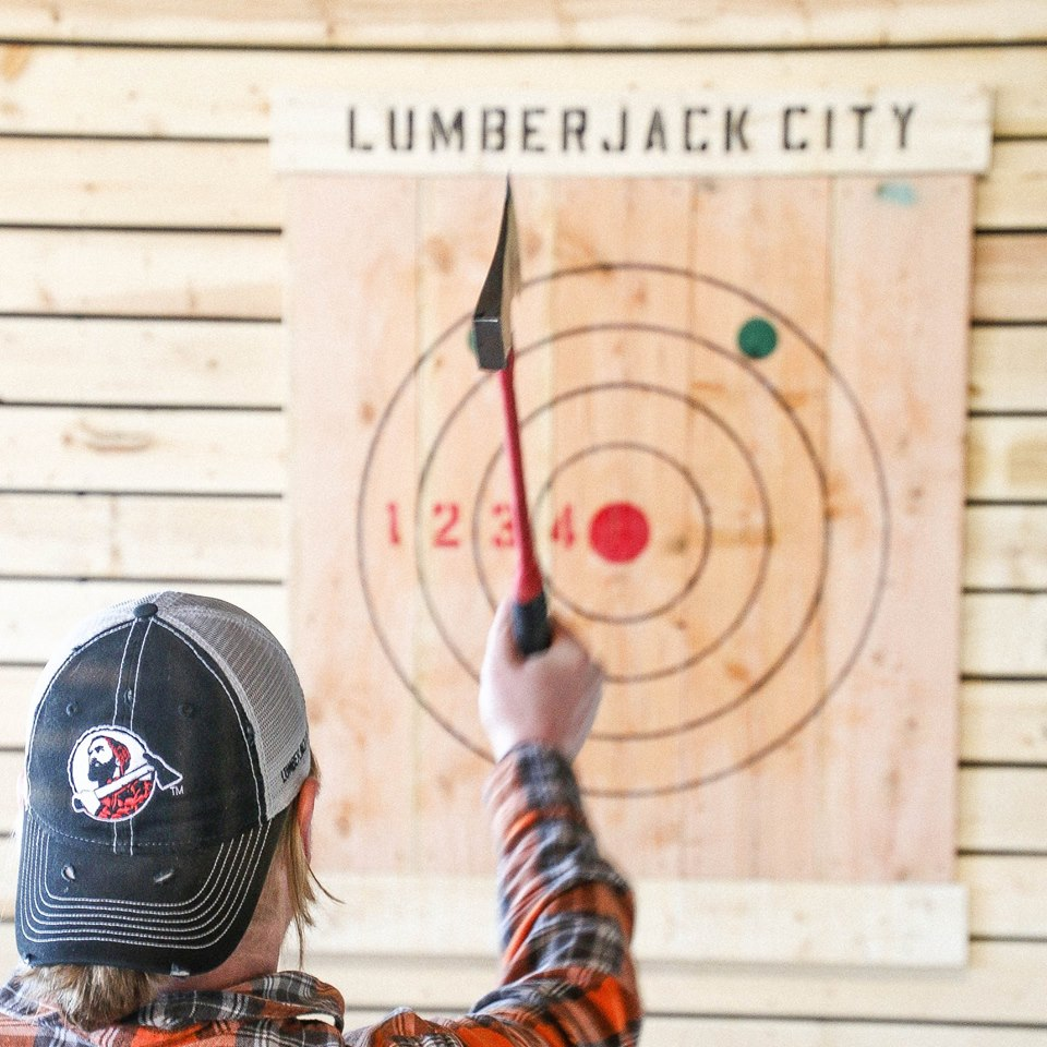 A person throws an axe at Lumberjack City