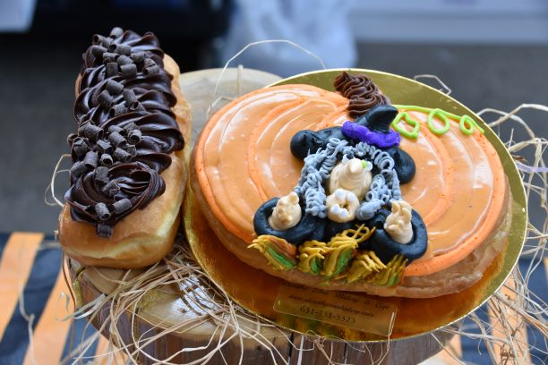 The decorated Witches Brew Donut from Dorothy Ann's Bakery & Cafe a pumpkin-shaped raised donut filled with a pumpkin cheesecake stuffing and Grandma G's ginger snap cookie crumble and a pumpkin pie spiced icing on top.