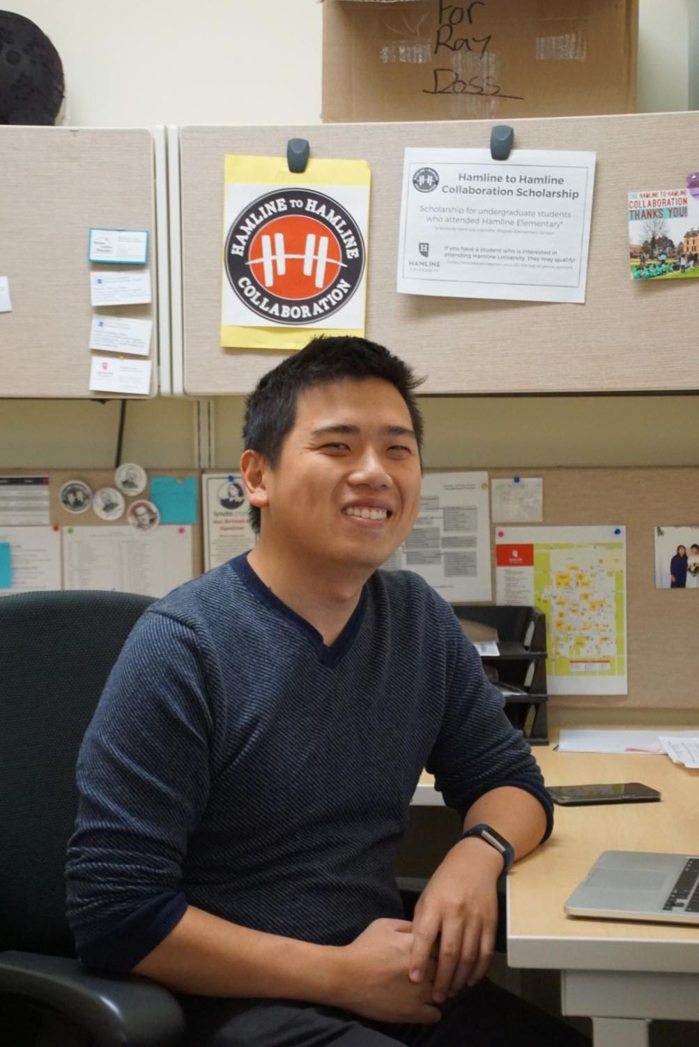 yang sitings at his new desk and poses for a picture.