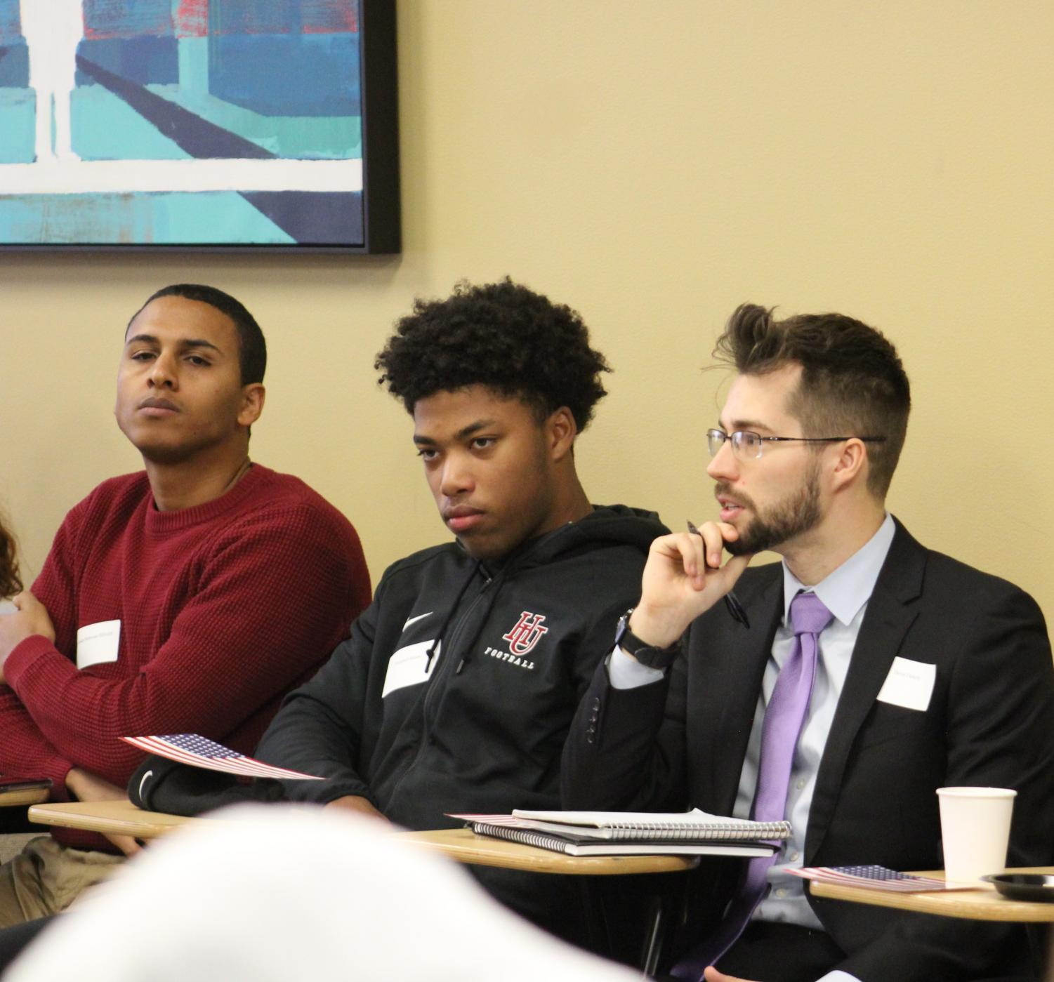 Hassan Mahmoud Jiddah, Manny Moton and Devan Flaherty listen intently to ongoing discussion.