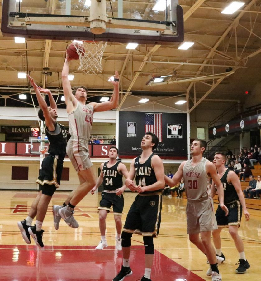 Ethan Scheuring, senior forward, scores during an opening in the first half of a men's basketball game.