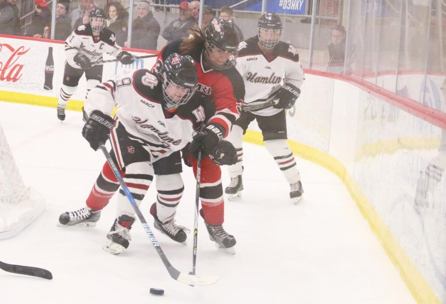 Hamline+sophomore+Jordan+Hansen+Fights+for+puck+control+behind+the+goal+during+the+quarterfinal+game+of+the+NCAA+DIII+Playoffs.