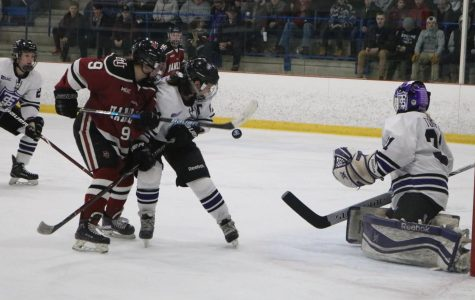 Sophomore Jordan Hansen fights for control of the puck in a game against St. Thomas on March 2.