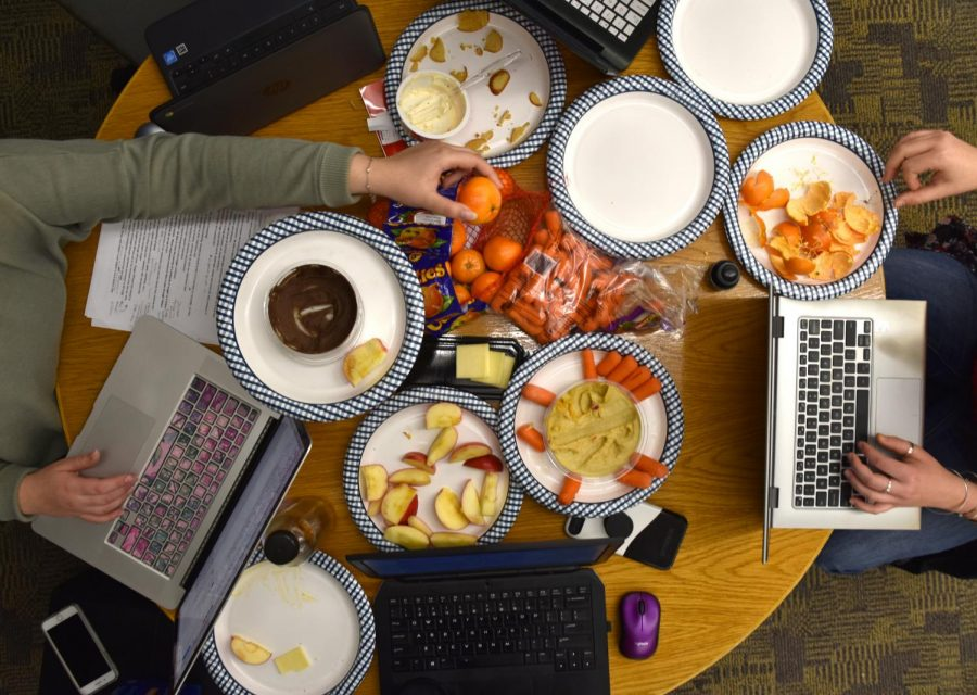 The editorial board of Canvas in the midst of editing with half-eaten snacks cluttering the space.