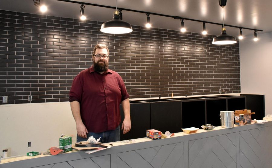 Owner Micah Sveja stands behind the future bar, waiting for its granite countertop.