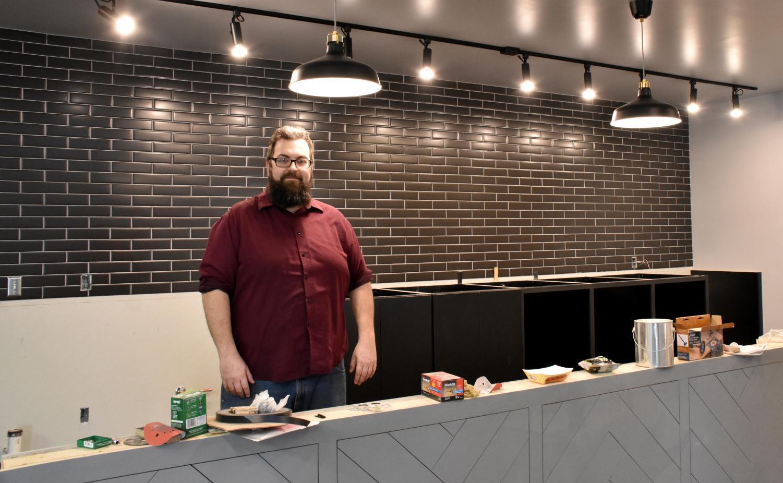 Owner Micah Sveja stands behind the future bar, waiting for its granite countertop.