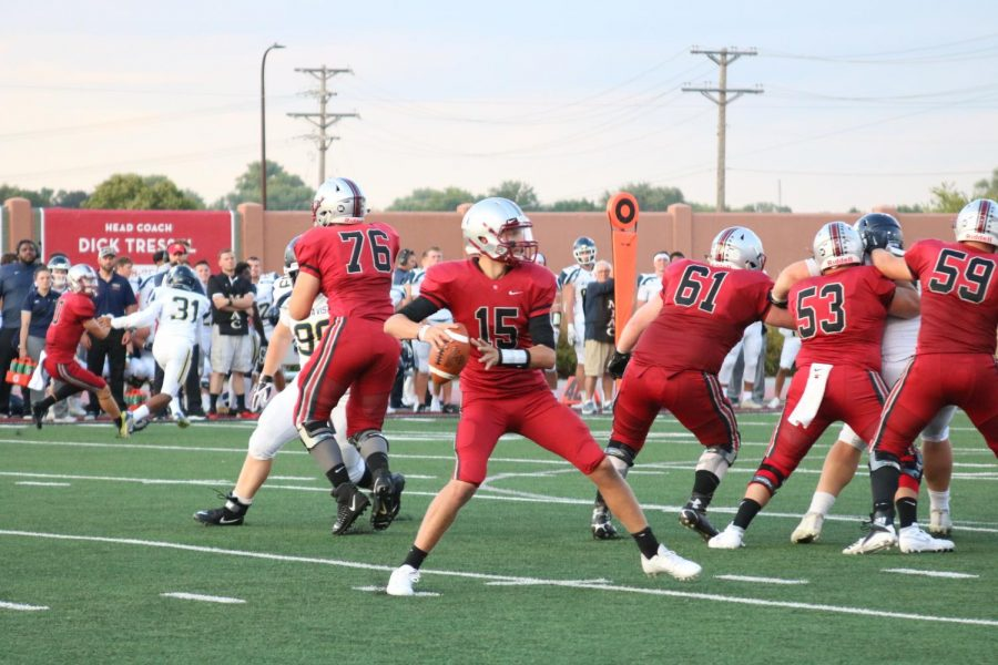 Junior quarterback Connor Leavens (#15) readies to pass as his offensive line holds the defense back.