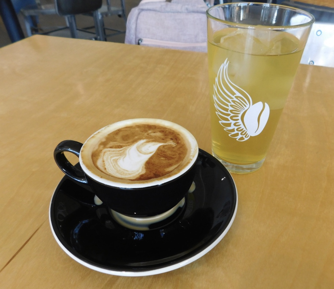 This Mango Green Iced Tea served in a small glass and this cappuccino, made of micro-foamed steamed milk and espresso are two items on BlackStack's menu.