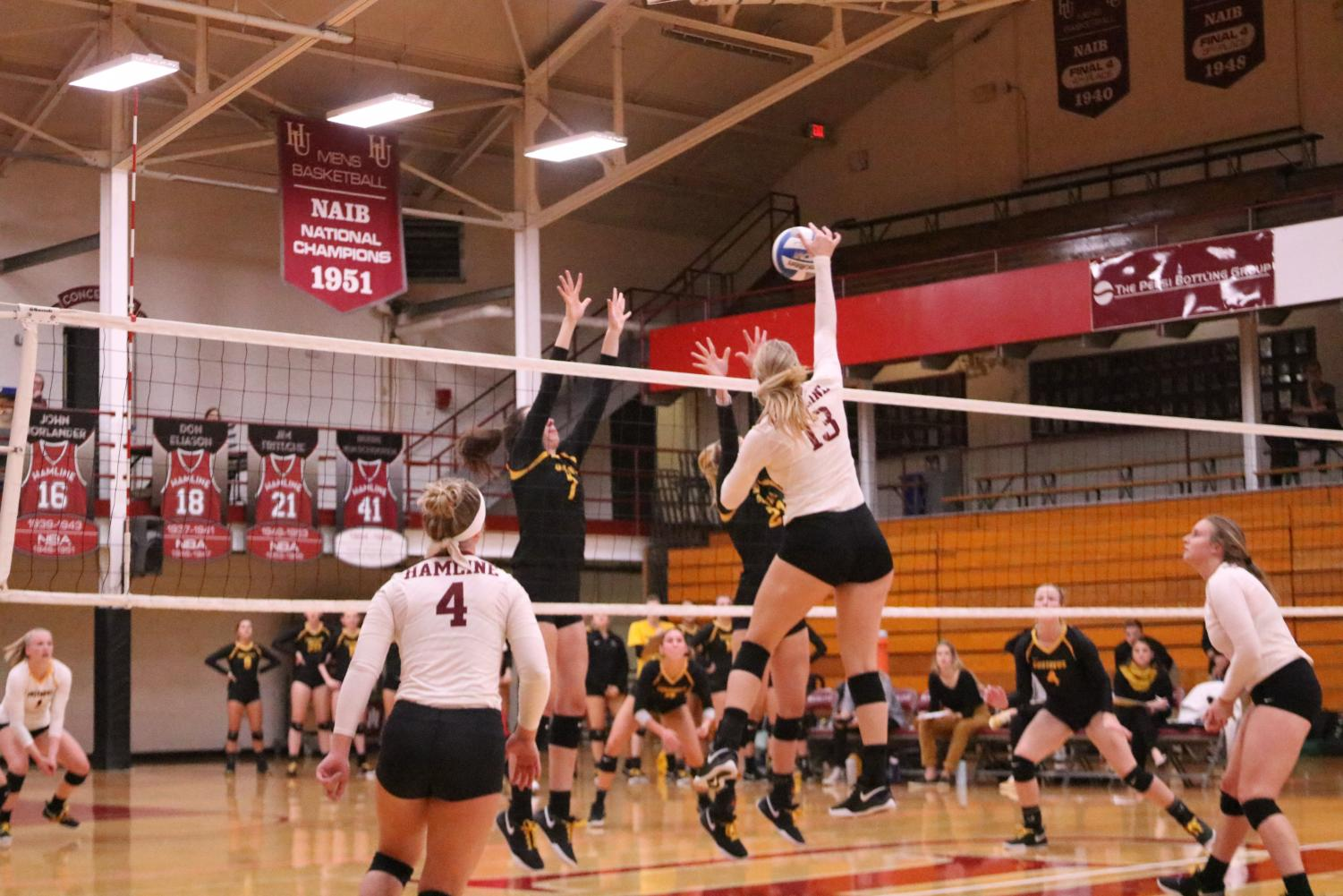 Junior Madison Hurrle tries to hit the ball past two Gustavus Adolphus blockers during a game on Oct. 5.