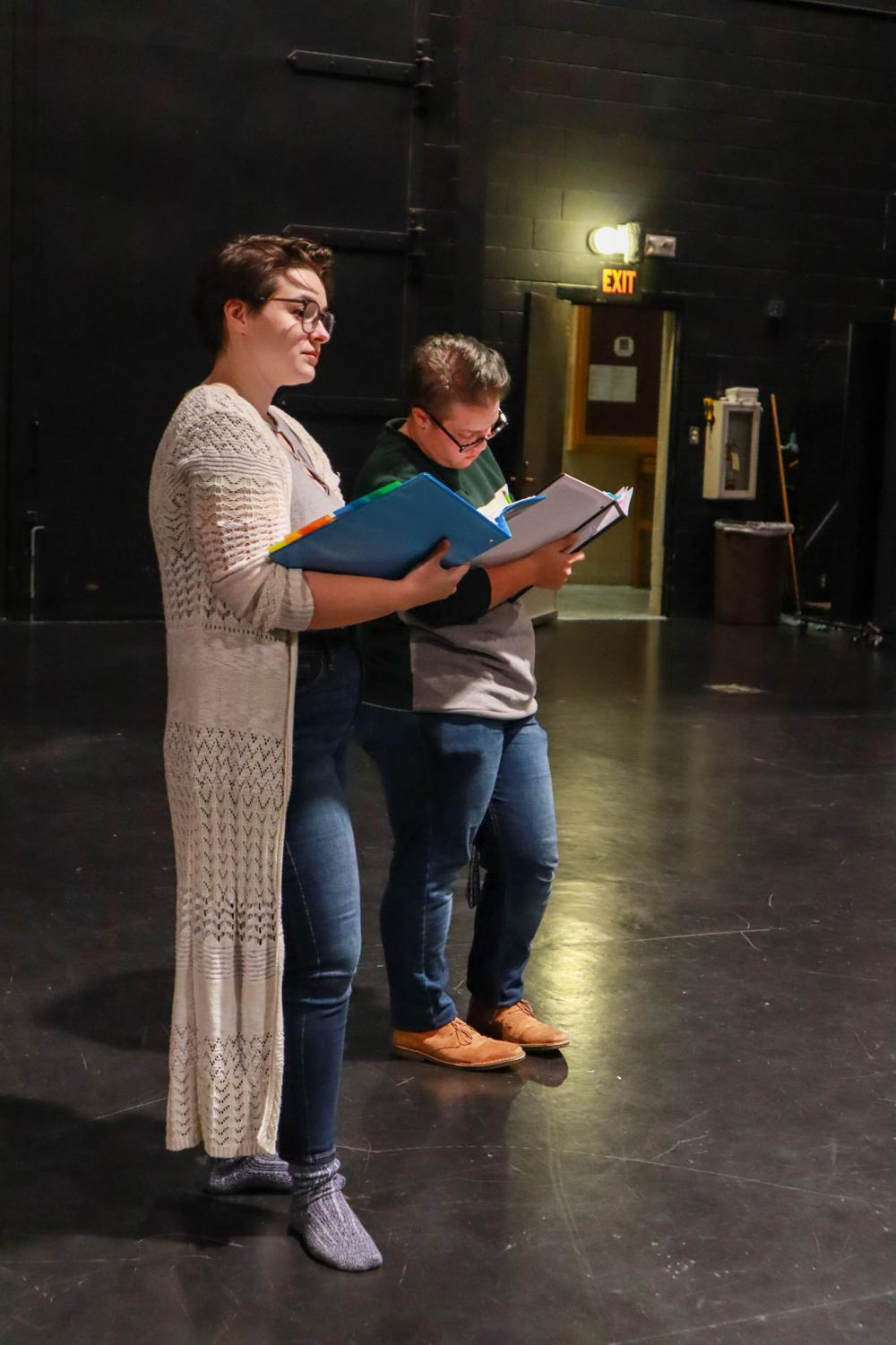 From left, senior Hannah Coleman and senior Aaron Lembi check scripts during an early rehearsal for Hamline's fall play, Iphigenia and Other Daughters, directed by Coleman
