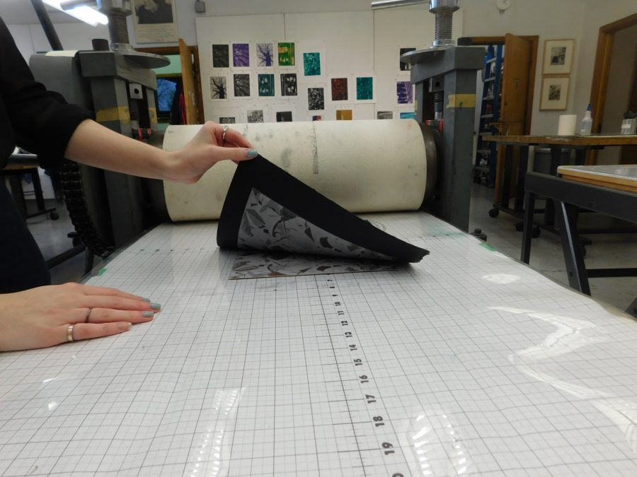 The black paper is lifted up slowly to reveal the printed design. The original design plate remains on the surface. This can be repeated multiple times for color variations.