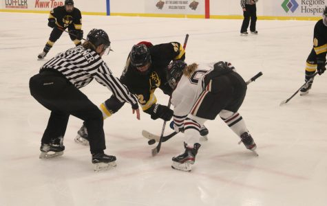 Senior Jordan Hansen fights opponent during face-off.