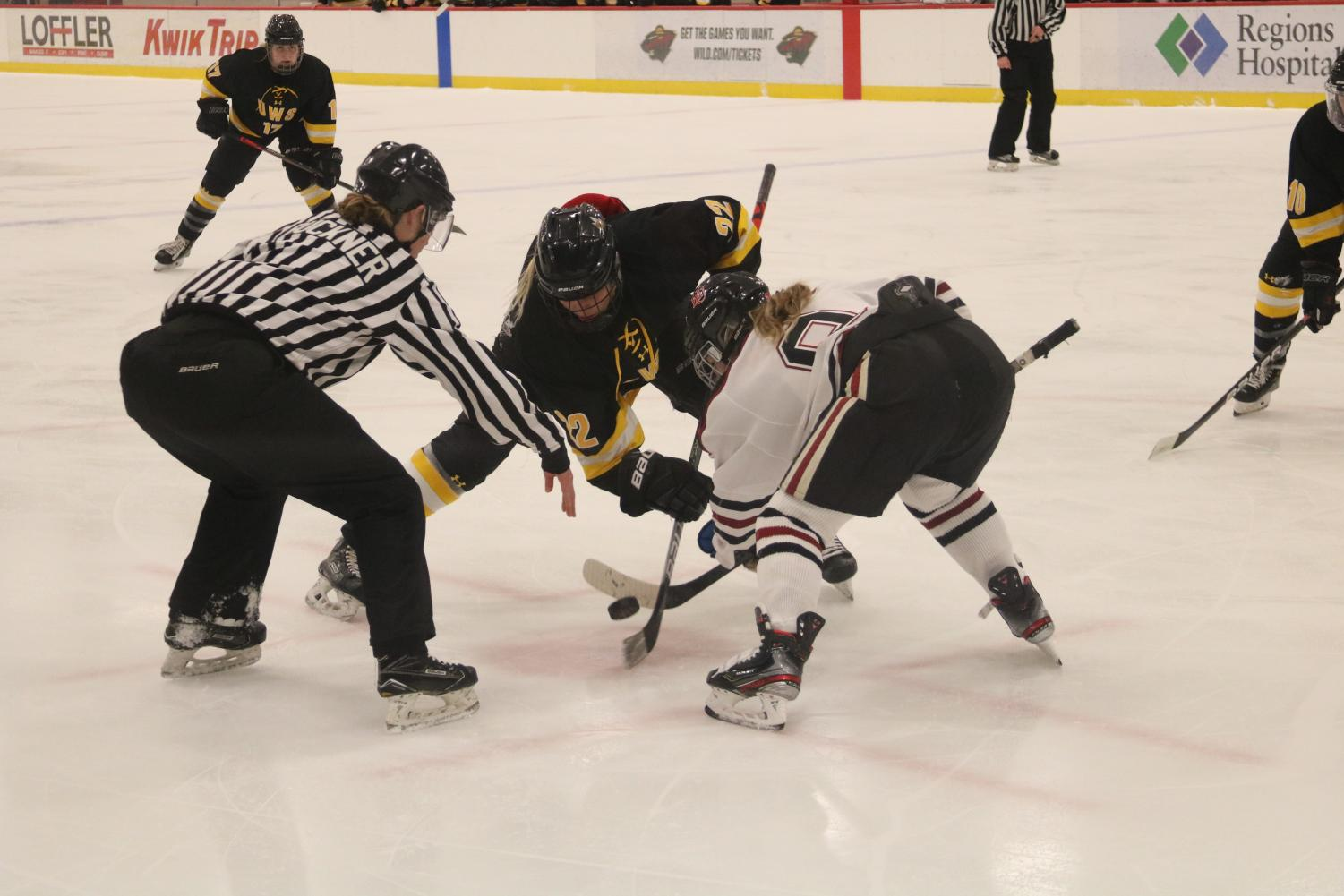 Senior Jordan Hansen fights opponent during face-off.