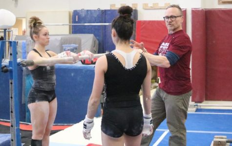 Coach Doug Byrnes talks with sophmores Savannah Tafolla and Katie Viles before starting to work on some uneven bars elements.