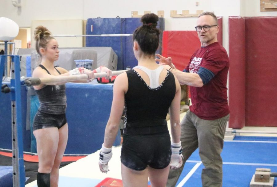 Coach+Doug+Byrnes+talks+with+sophmores+Savannah+Tafolla+and+Katie+Viles+before+starting+to+work+on+some+uneven+bars+elements.