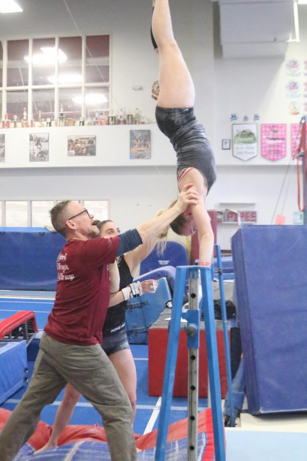 sophmore Katie Viles and Coach Byrnes spot Savannah Tafolla while she works on a handstand with the practice bar.
