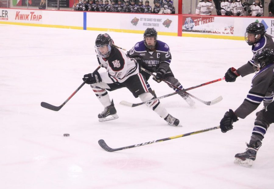 First-year Sophie Rausch pulls the puck out of the reach of three opponents during a match against St. Thomas on Feb. 14.