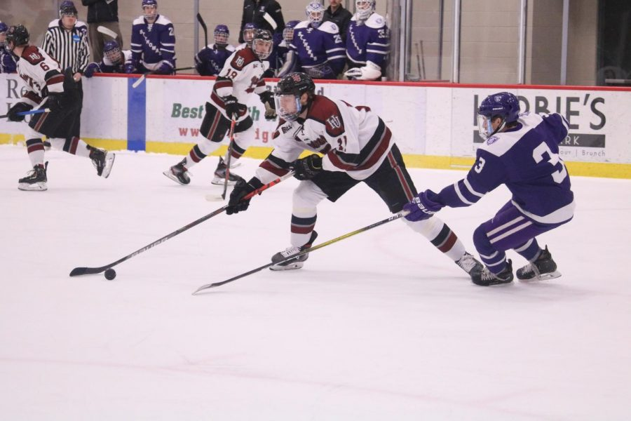 Senior and Men's Hockey Captain Brady Crabtree reaches for the puck in a Feb. 15 match against St. Thomas. This was Crabtree's last game as a student athlete.