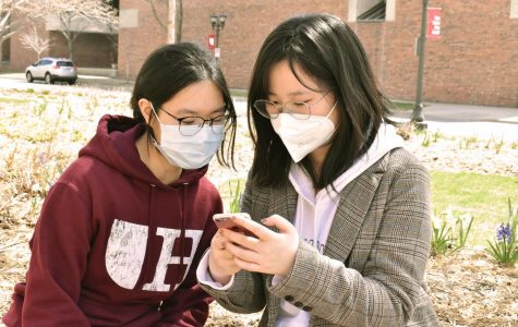 Juniors Ziqiao Ma and Zhaoying Chen share a moment in the sun outside of Drew Residence Hall, both wearing face masks.