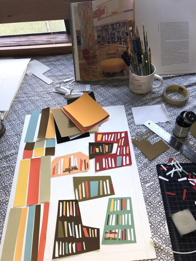A vertical photograph showing a partly-completed piece of artwork. Colored paper cut into strips are placed on a white poster as the artist makes decisions about how to visually construct their artwork. In the background are pictured art materials such as glue, paintbrushes, and cutting tools. Also in the background is a photo of a library or reading room being used as reference for the artwork.