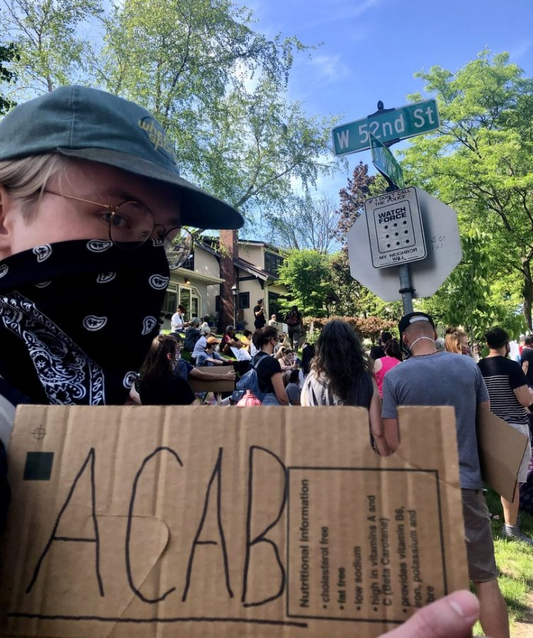 """Junior Peter Hanson at protest with """"ACAB"""" sign"""