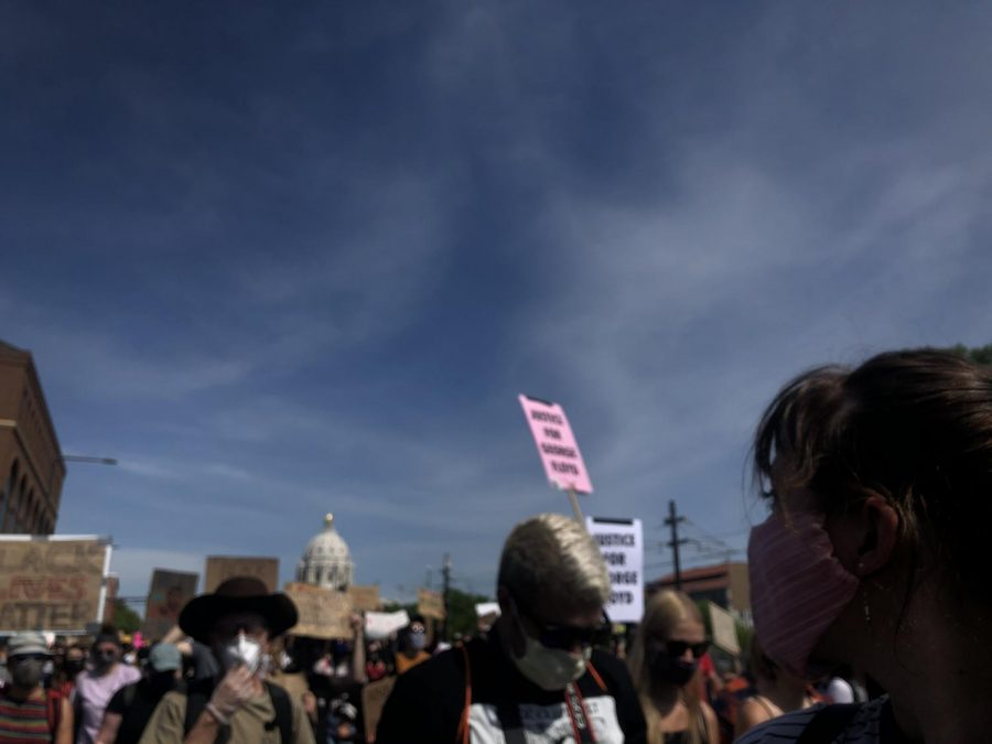 A crowd of protesters against a blue sky in front the Minnesota State Capitol