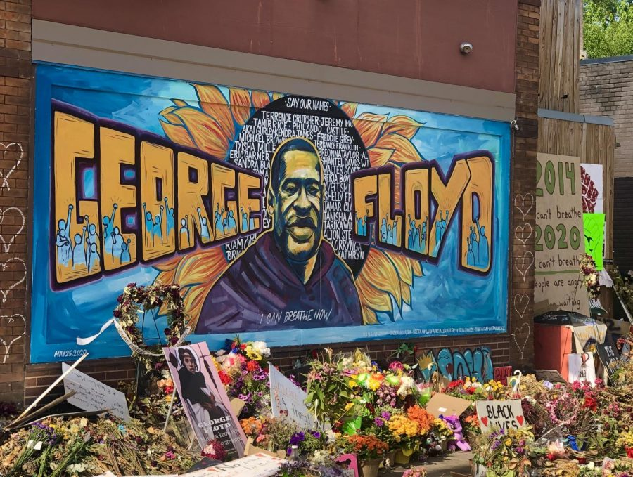 A painted mural of George Floyd surrounded by flowers and other gifts at the intersection of 38th and Chicago in Minneapolis