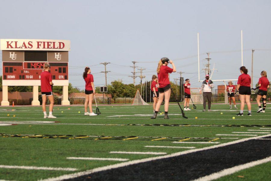 The women's lacrosse team practicing passing on the field at Klas Field