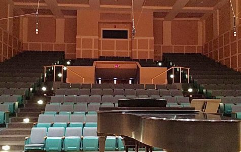 An empty Sundin Hall looks barren with no students and just a piano on stage