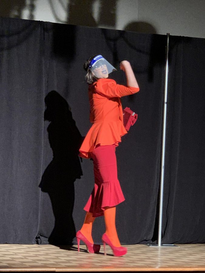 A+perfomer+at+the+drag+show+dressed+up+as+Velma+from+scooby+doo+while+wearing+a+face+shield