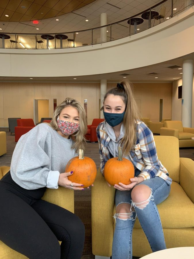 Two students show off their pumpkins in the Anderson center