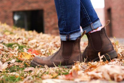 A pair of brown boots against a background of orange and red leaves