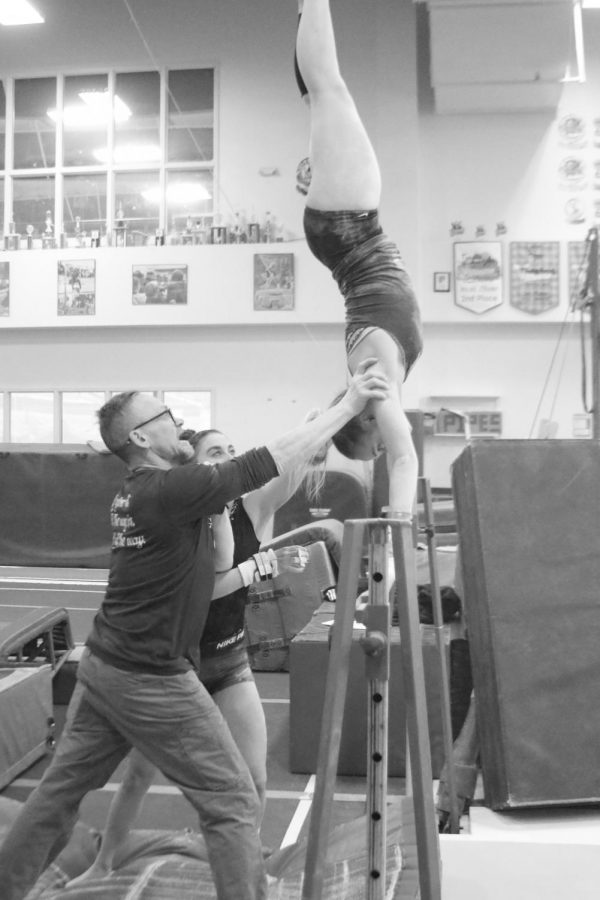 A hamline coach helping an athelete work on their handstand on the practice bar