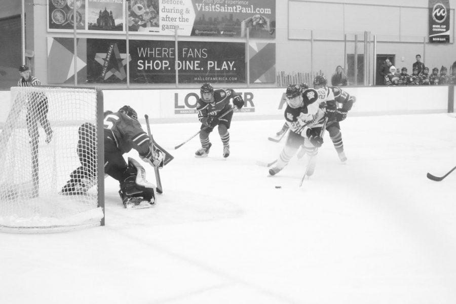 A Hamline Men's hockey game with a Hamline player about to shoot on St. Thomas's goal