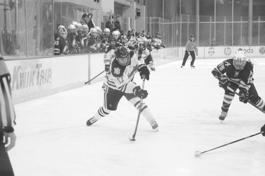 Hamline Men's Hockey against Augsburg. Taylor Curtis is taking a shot at Augsburg's goal