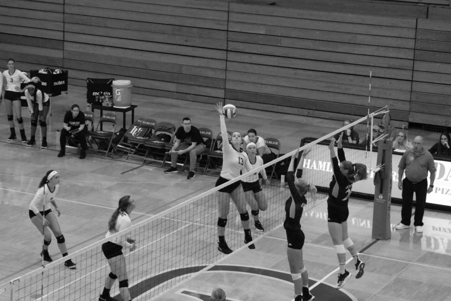 A Women's volleyball game with a Hamline player about to spike over the net