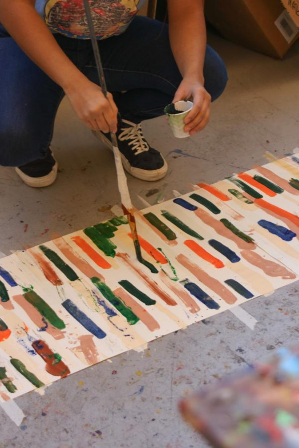 student paints on the floor with an elongated paintbrush.