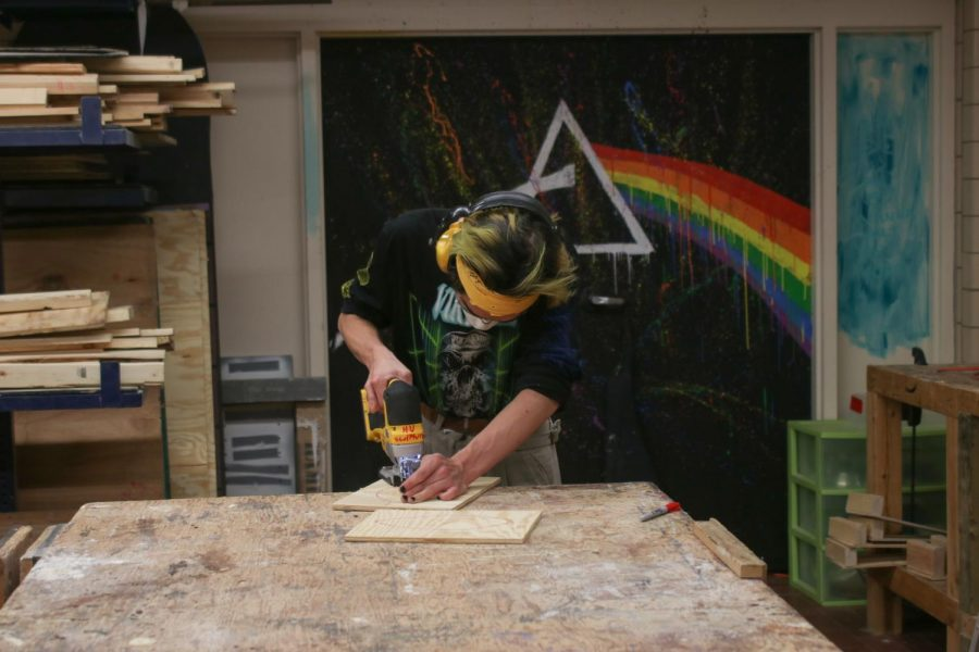 A student is cutting a piece of wood in the studio