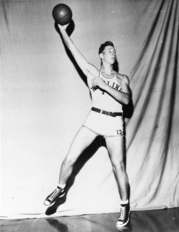 Black and white photograph of Hamline basketball player holding a basketball in this hand