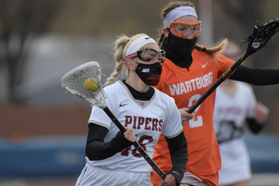Aidan StromdahlJunior Tara Deleo maintains posession during the women's lacrosse match against Wartburg college.